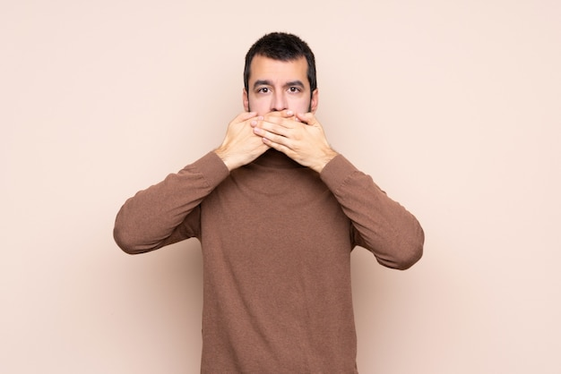 Man over isolated wall covering mouth with hands