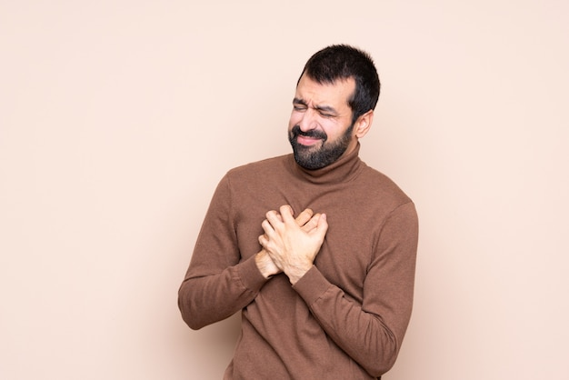 Man over isolated wall having a pain in the heart