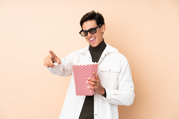 Man over isolated wall with 3d glasses and holding a big bucket of popcorns while pointing away