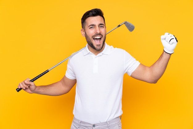 Man over isolated yellow wall playing golf and celebrating a victory