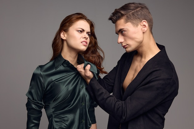 A man in a jacket holds a woman by the collar on a gray background abuse domestic violence. high quality photo