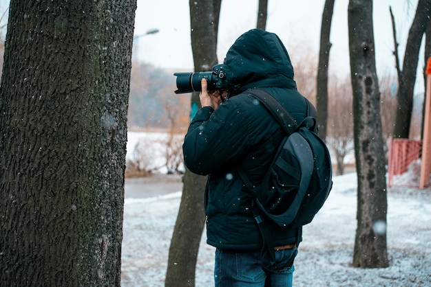 A man in a jacket with a hood and a briefcase on his back, holding a camera and taking pictures of a tree