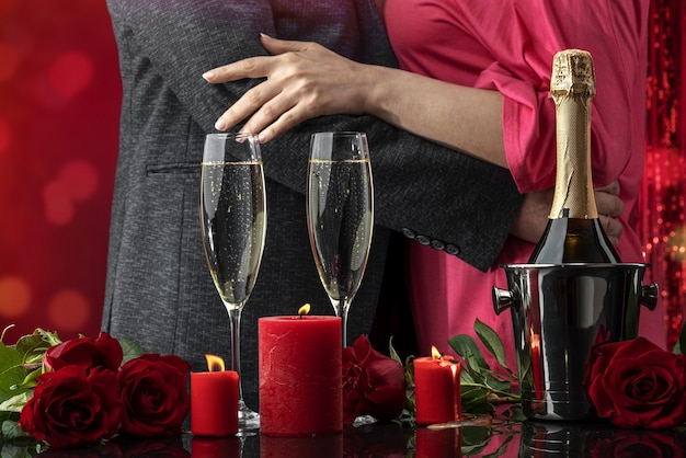 A man in a jacket and a woman in a pink dress are dancing hugging candles and luxury roses