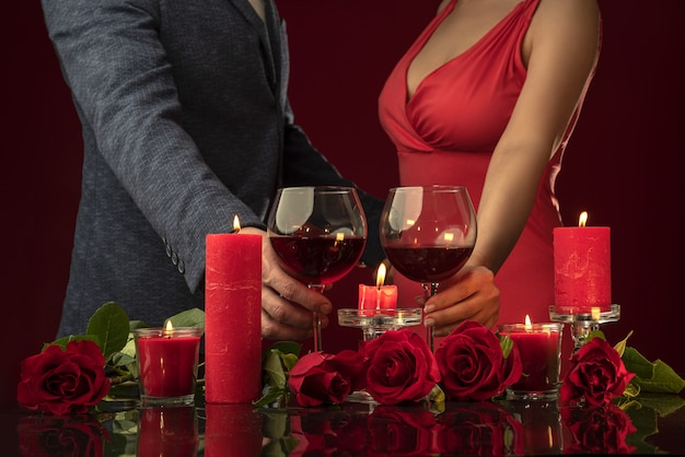 A man in a jacket and a woman in a pink dress are holding glasses of red wine