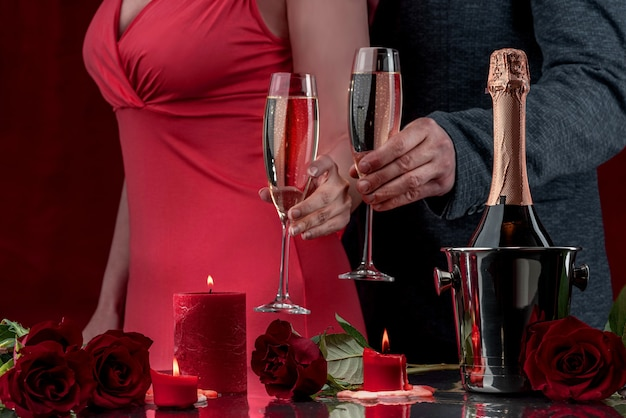 A man in a jacket and a woman in a pink dress are holding glasses of sparkling wine