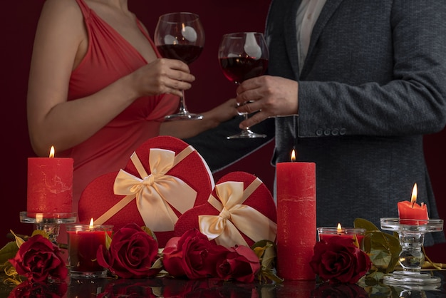 A man in a jacket and a woman in a pink dress are holding hands and drinking wine