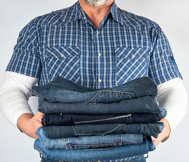 Man in jeans and blue plaid shirt holding a pile of jeans