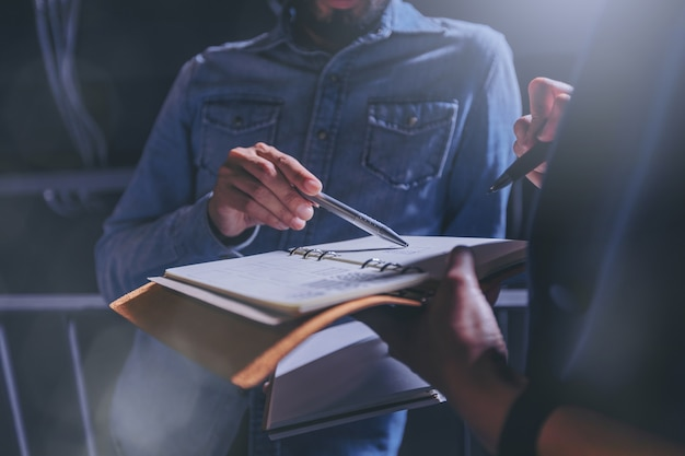Man in jeans gives advice on work in a notebook with colleagues in office.