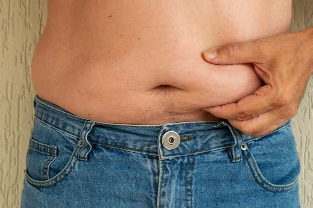 Man in jeans holding his belly. abdominal fat.