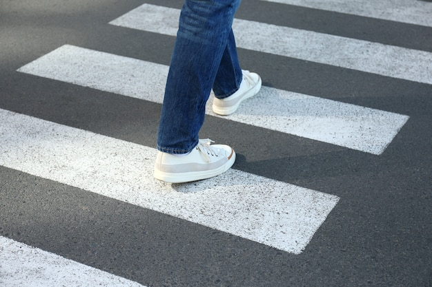 Man in jeans and sneakers walking on crosswalk.