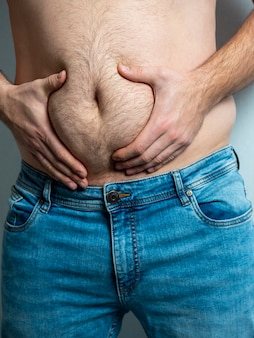 The man in jeans squeezes his hairy, flabby, fat stomach.