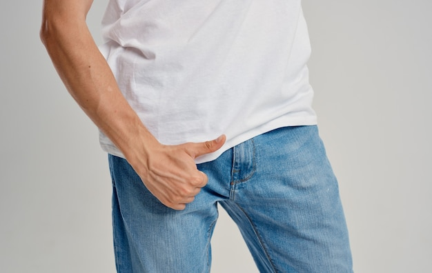 A man in jeans and a t-shirt shows a thumb up below the belt