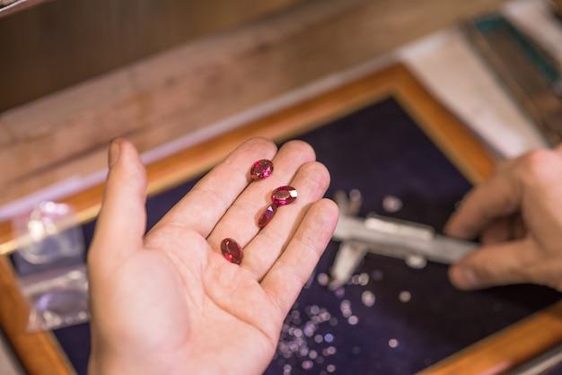 Man jeweler makes an accurate measurement of a gem using a caliper