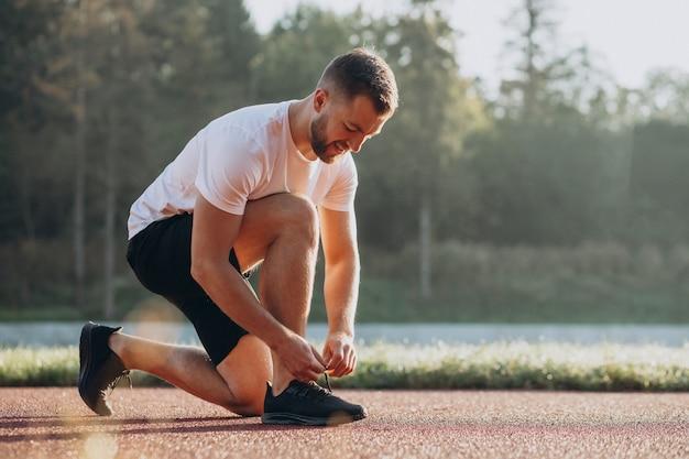 Man jogger tying shoelaces at stadim