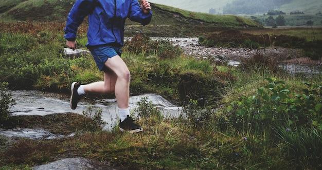 険しい地形で一人でジョギングする男