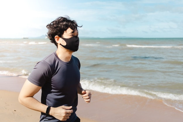 Man jogging on the beach with mask in summer morning