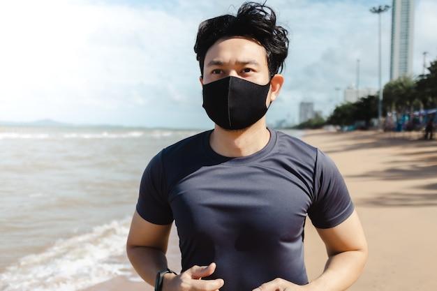 夏の朝にマスクでビーチでジョギング男