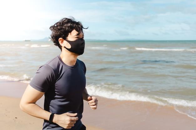여름 아침에 마스크를 쓰고 해변에서 조깅하는 남자