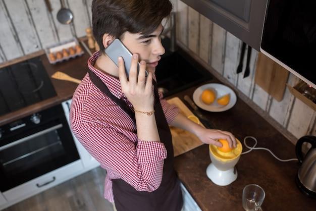 オレンジを絞り、電話で話す男