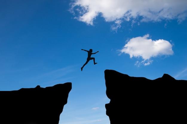 L'uomo salta attraverso il divario tra hill.man saltando sulla scogliera sullo sfondo del tramonto, idea di business concept