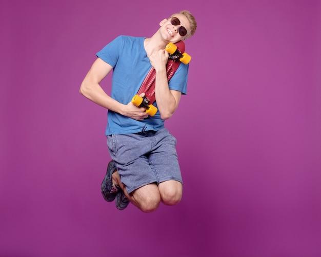 Человек прыгает с скейтбордом в руке на фиолетовом фоне