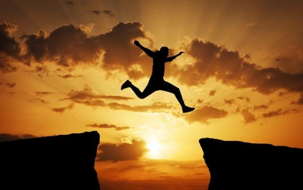ある岩から別の岩にしがみつくまでの隙間を飛び越える男。夕焼けの燃えるような背景にギャップのある岩を飛び越える男。デザインの要素。
