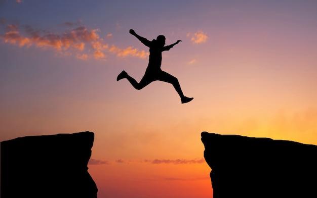 남자가 한 바위에서 다른 바위에 달라 붙기 위해 틈새를 뛰어 넘습니다.