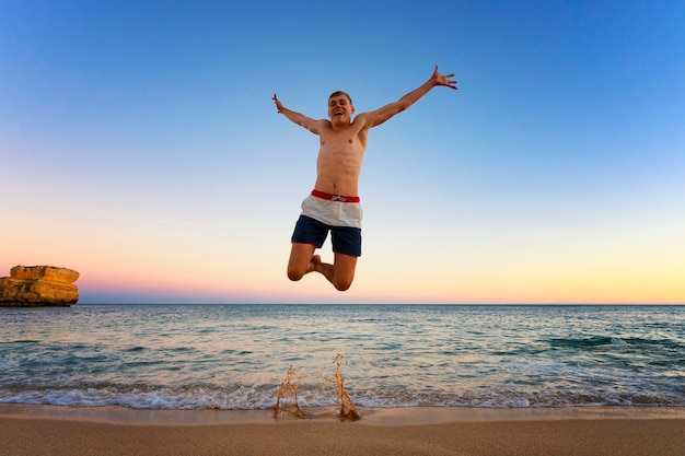 Мужчина прыгает на пляже камило, португалия