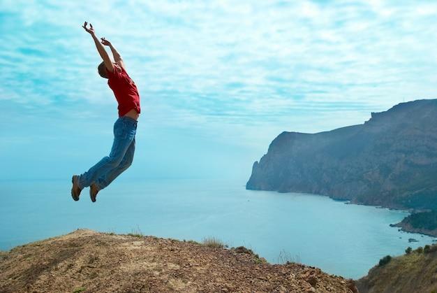 Человек прыгает со скалы против моря и горы с голубым небом