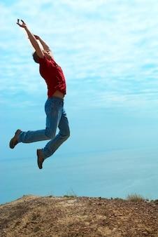 青い空と海と山に対して崖をジャンプする男