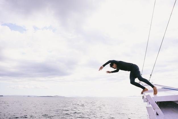 Человек прыгает с лодки в море