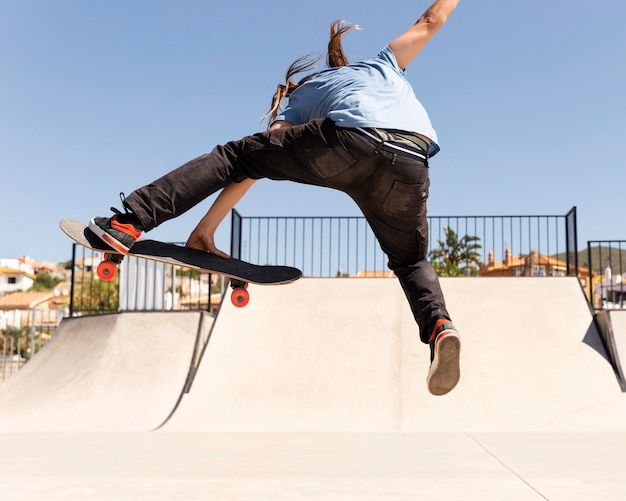 Человек прыгает высоко с полным выстрелом скейтборда