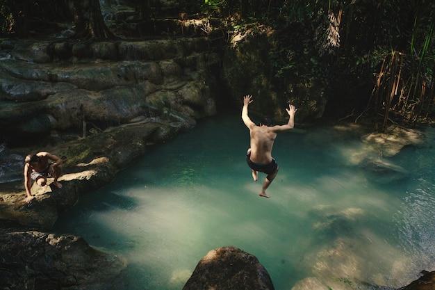 自然の池に飛び込む男