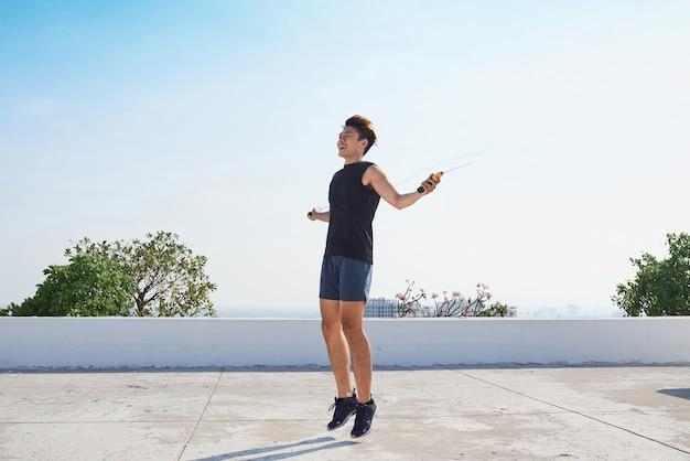 Человек прыгает на скакалке. молодые азиатские мужчины спуска с голым торсом прыгают на скакалке на открытом воздухе