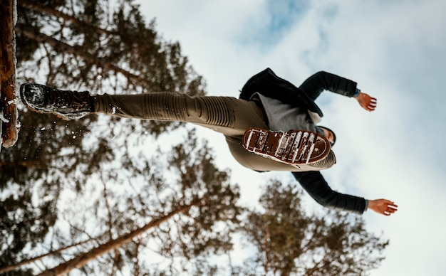 Человек прыгает на открытом воздухе на природе зимой