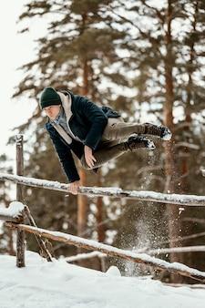 冬に屋外でジャンプする男