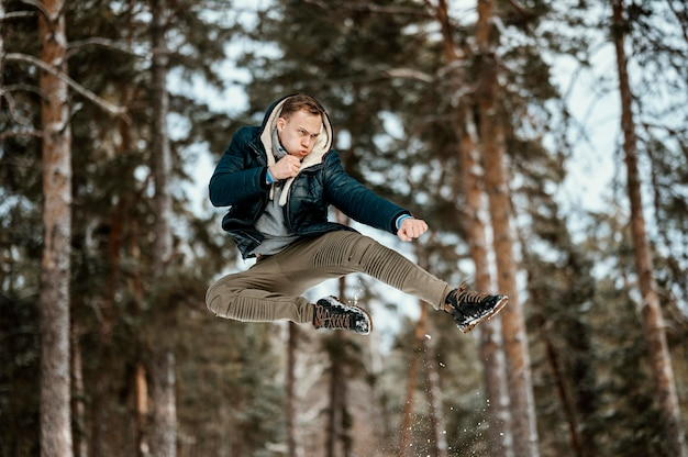 Man jumping outdoors in nature during winter