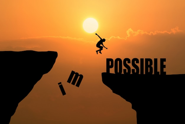Человек прыгает над невозможным или возможно над утесом на фоне заката, концепция бизнес-концепции