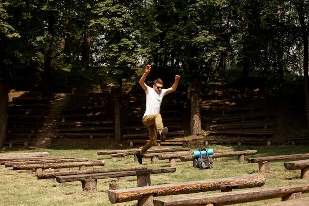 Человек прыгает через деревянные скамейки