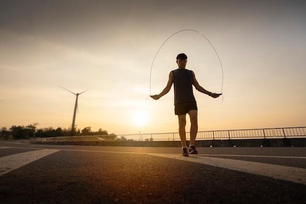 太陽の光の中で縄跳びをする男。健康的な生活様式。