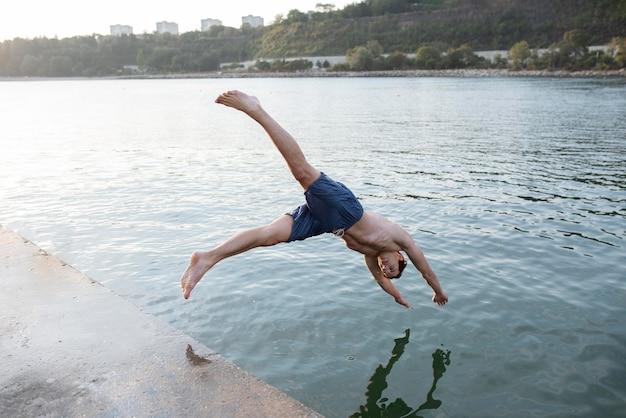 Uomo che salta in acqua a tutto campo
