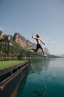 湖で喜んでジャンプする男