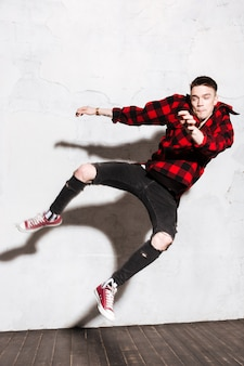 Man jumping with plaid shirt and ripped jeans