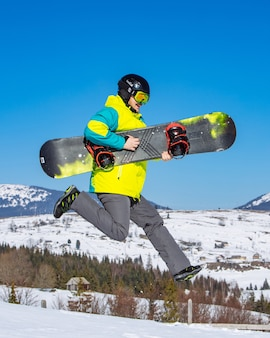 배경에 손 산에서 스노우 보드와 함께 점프 하는 남자. 맑은 날. 재미