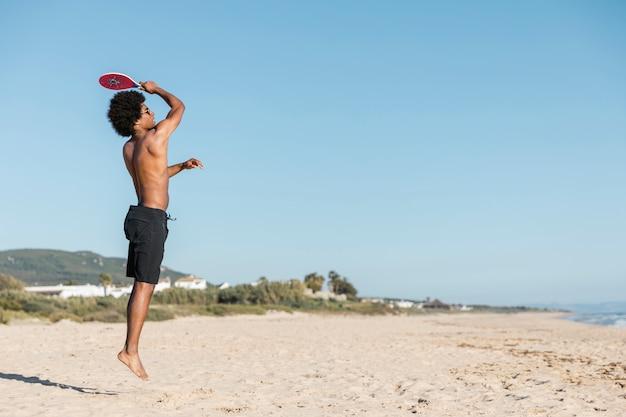 男はビーチでテニスラケットでジャンプ