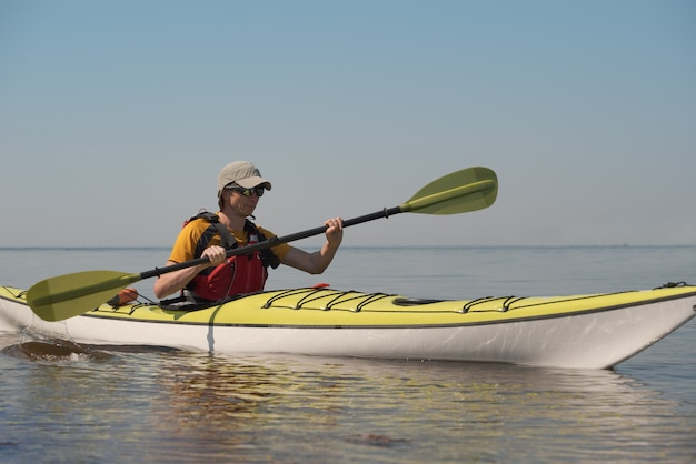 A man on a kayak glides on the surface of the water. water sports theme