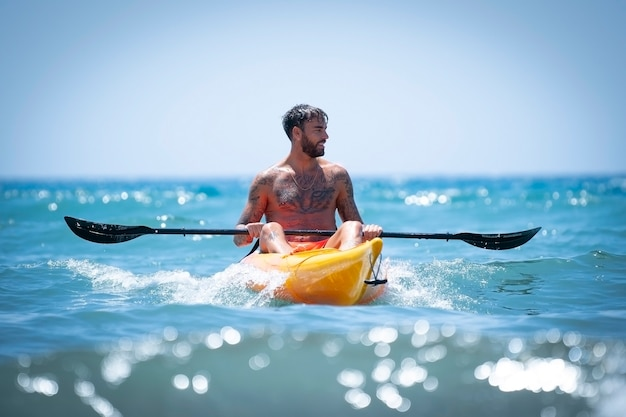Man kayaking on the beach during summer vacation