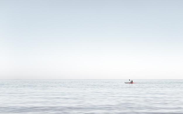 바다의 매우 잔잔한 물에서 카약을 타는 남자에게 해의 이른 오후에 카약을 타는 남자