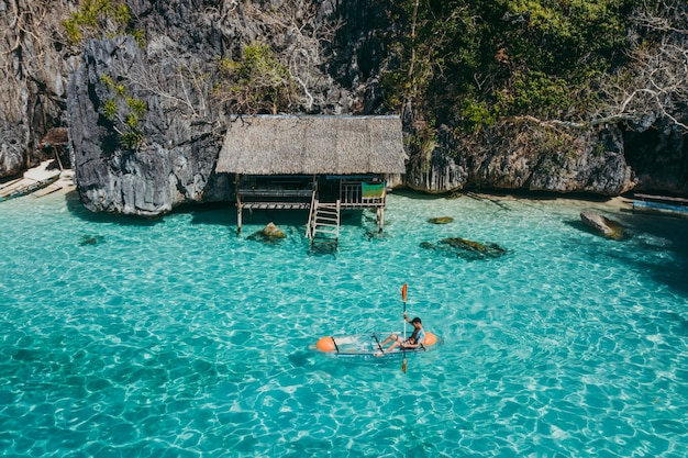 Man kayaking in the twin lagoon between the rocks and fishermen houses, enjoying the landscape. concept about travels in the philippines