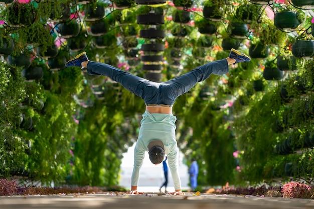 Мужчина держит равновесие на руках в яркой цветочной арке с зонтиком на вокзале корниш. доха, катар. понятие о здоровье и силе.